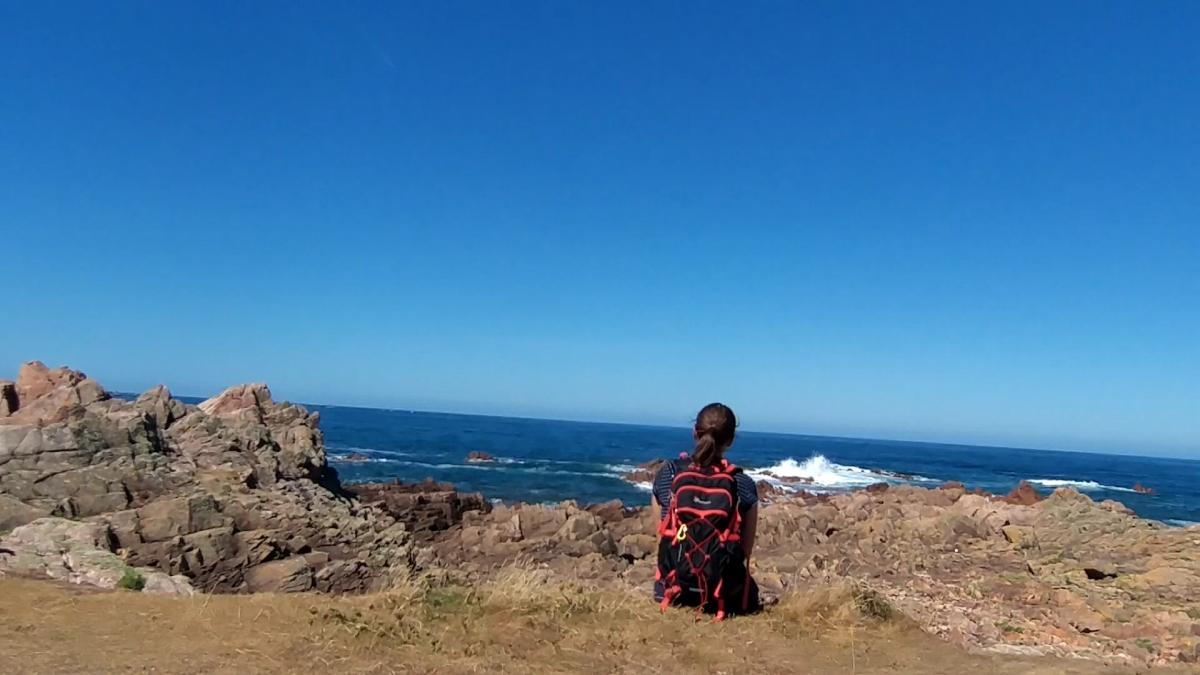 Wanderin sitzt am Meer